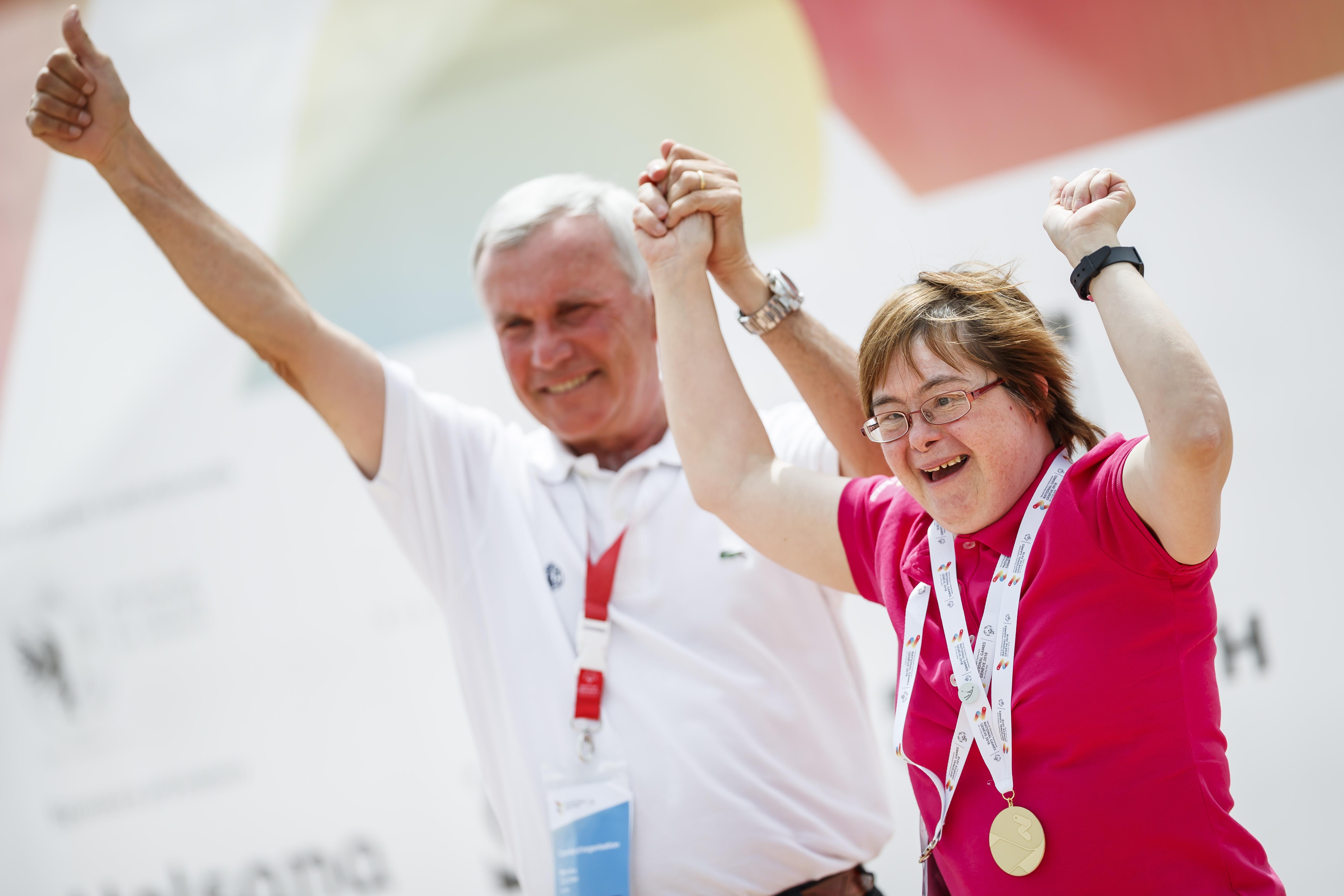 Athletin und Volunteer jubeln an der Medaillenfeier zusammen