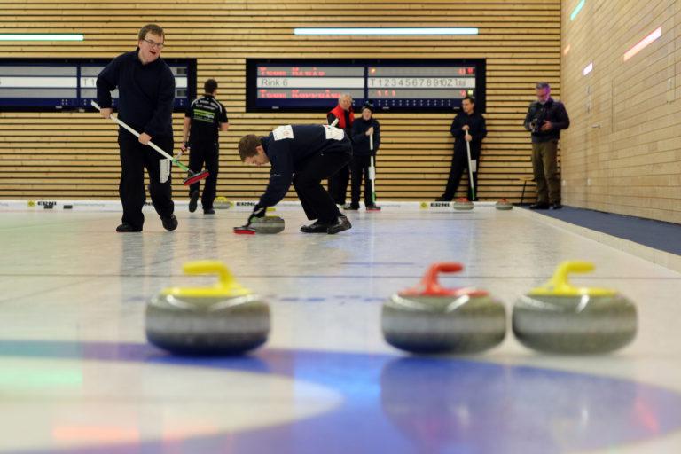 des hommes jouent du curling
